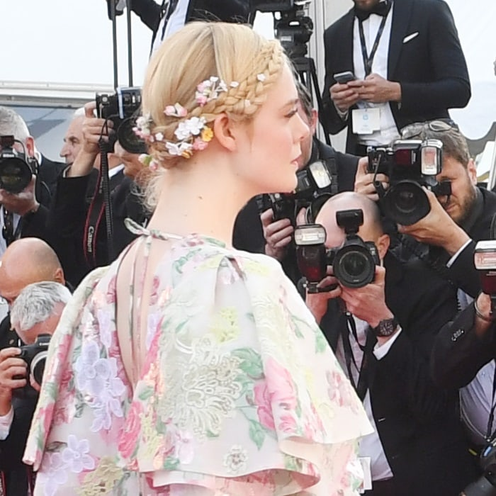 Elle Fanning accessorized her milkmaid braids with tiny daisies, roses, and white flowers