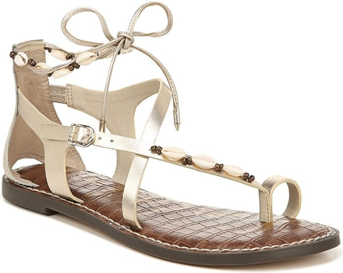 Cowrie shells and seed beads add festival-ready touches to a toe-loop sandal fashioned with asymmetrical straps and ankle ties