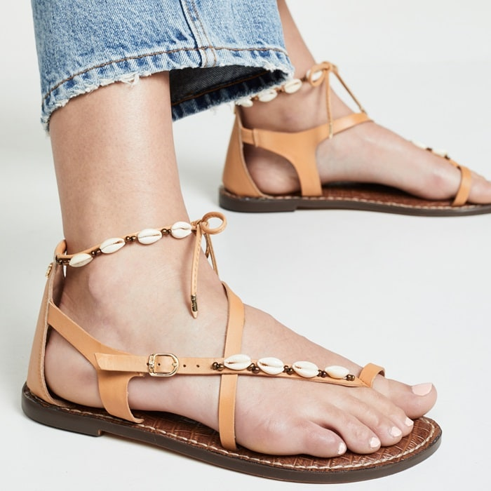 Flat sandals feature a leather upper with seashell charms
