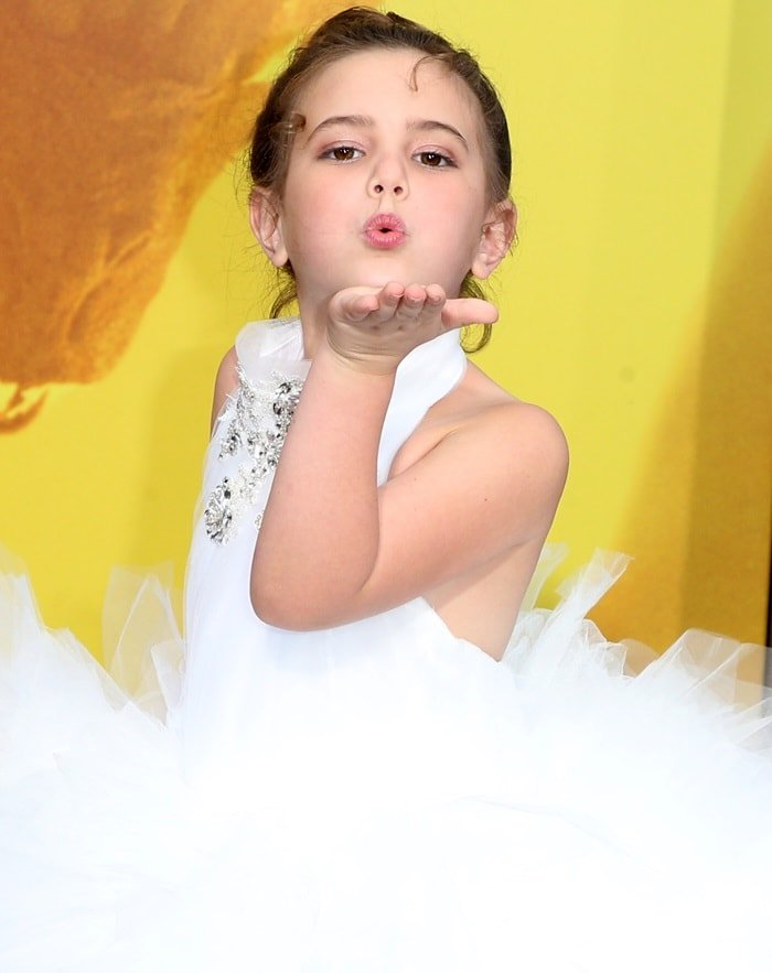 Lexi Rabe blows a kiss in a white feathered gown by Isabella Couture