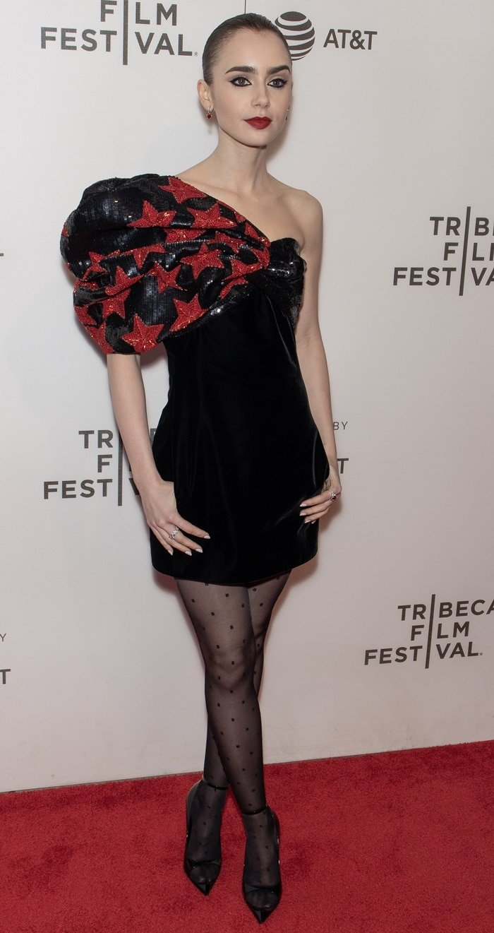 Lily Collins crossed her legs in black stockings