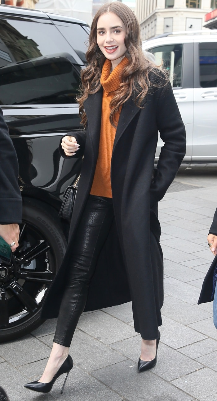Lily Collins promoted Tolkien in a spicy orange sweater from Dorothee Schumacher and leather pants in London on April 29, 2019