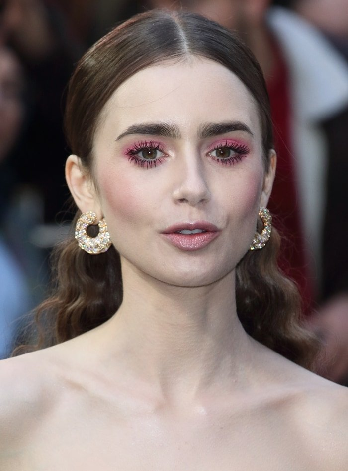 Lily Collins' hot pink eye makeup and gold hoop earrings