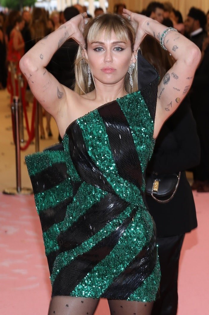 Miley Cyrus donned a one-shouldered black and green mini dress