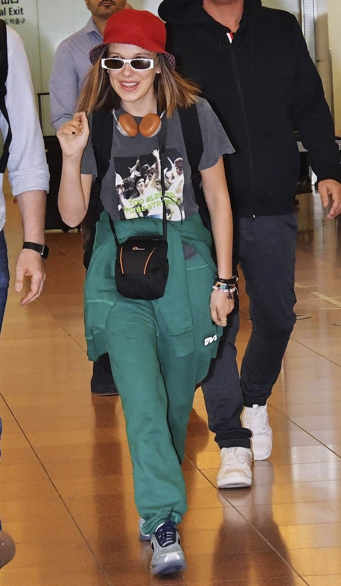 Stranger Things star Millie Bobby Brown arrives at Tokyo International Airport in forest green OVO sweatpants