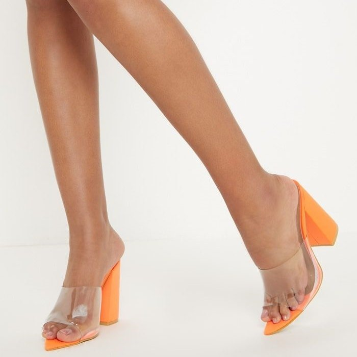 Brighten up your look with these affordable mules featuring a pointed toe with an orange block heel and clear strap