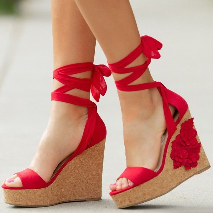 This red platform faux-cork wedge sandal features a flower applique and adjustable ankle ties