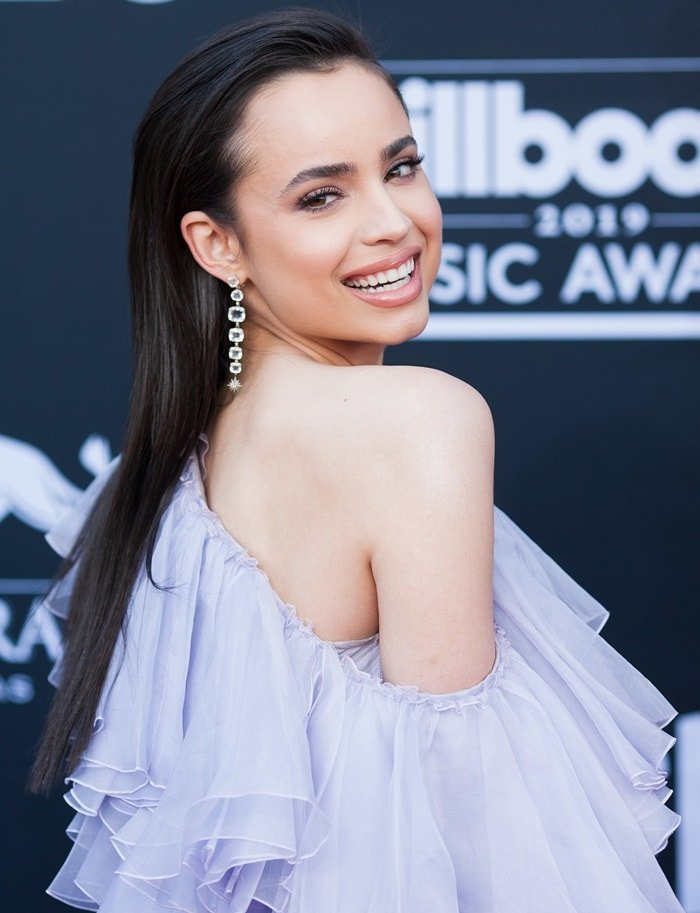 Sofia Carson showed off her Moonlight earrings in a one-shouldered, floor-length lavender gown