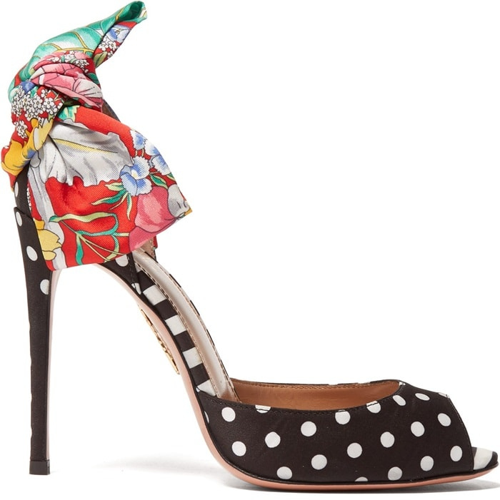 Crafted in Italy, the duo of fabrics is complemented by a stiletto heel and large bow with a gold-tone metal pineapple logo plaque on the sole