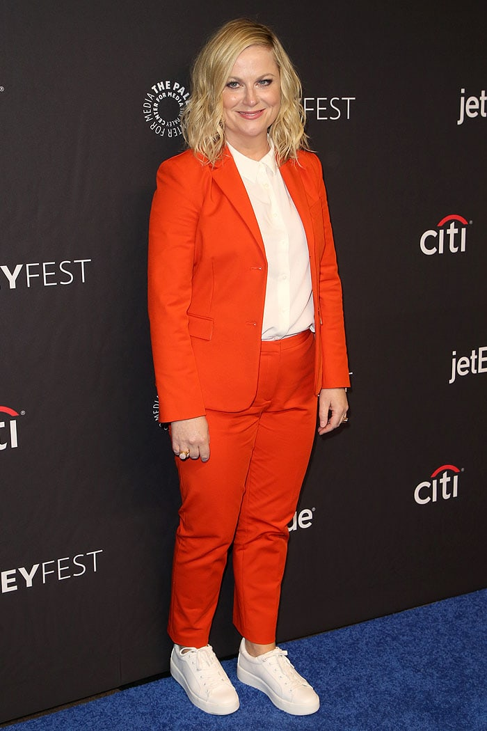 Amy Poehler in an orange pantsuit and white sneakers