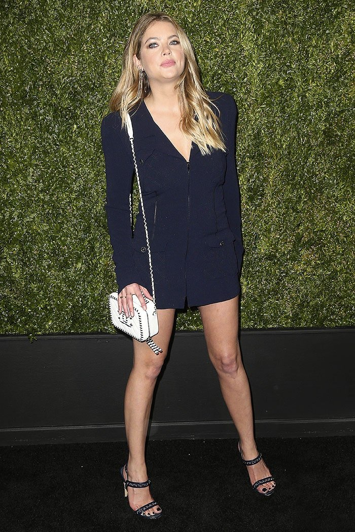 Ashley Benson wearing a Chanel Spring 2019 navy stretch-crepe jacket as a dress, a Chanel white-calfskin vanity case, and Chanel chain-embellished slingback sandals