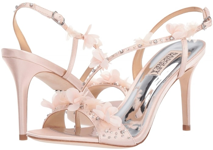 Sparkling crystals and 3D flowers embellish the svelte, swooping straps of a glamorous sandal lifted by a tall, tapered heel