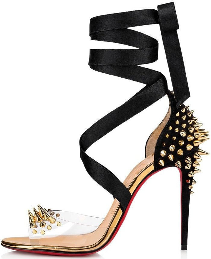Spikes at the heel and clear vamp add edge to a willowy stiletto sandal secured at the ankle with black ribbons and a bow at the back