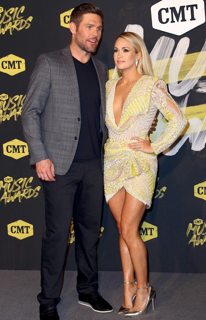 Carrie Underwood posed with Mike Fisher and flaunted all her assets in a long-sleeved yellow asymmetrical mini dress that featured a plunging neckline at the 2018 CMT Music Awards