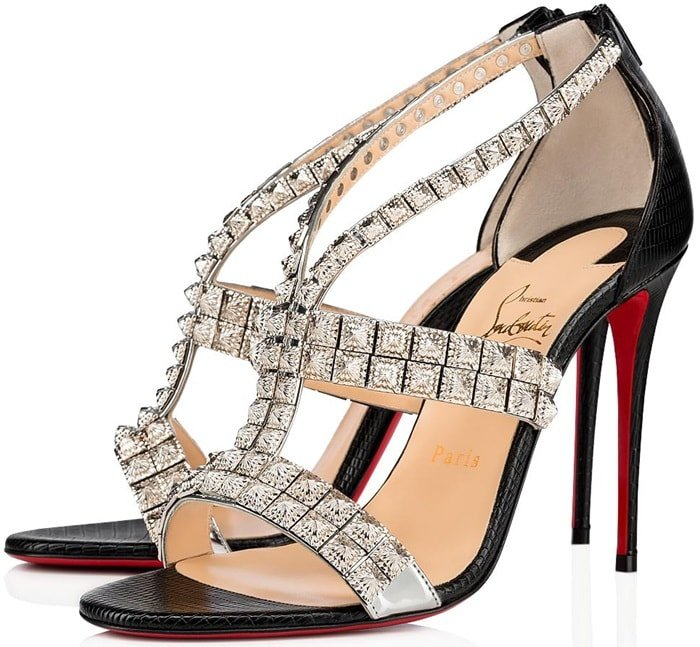 Glinting pyramid studs and reptile-embossed leather add rich texture to a strappy sandal finished with a willowy stiletto and that famed red sole