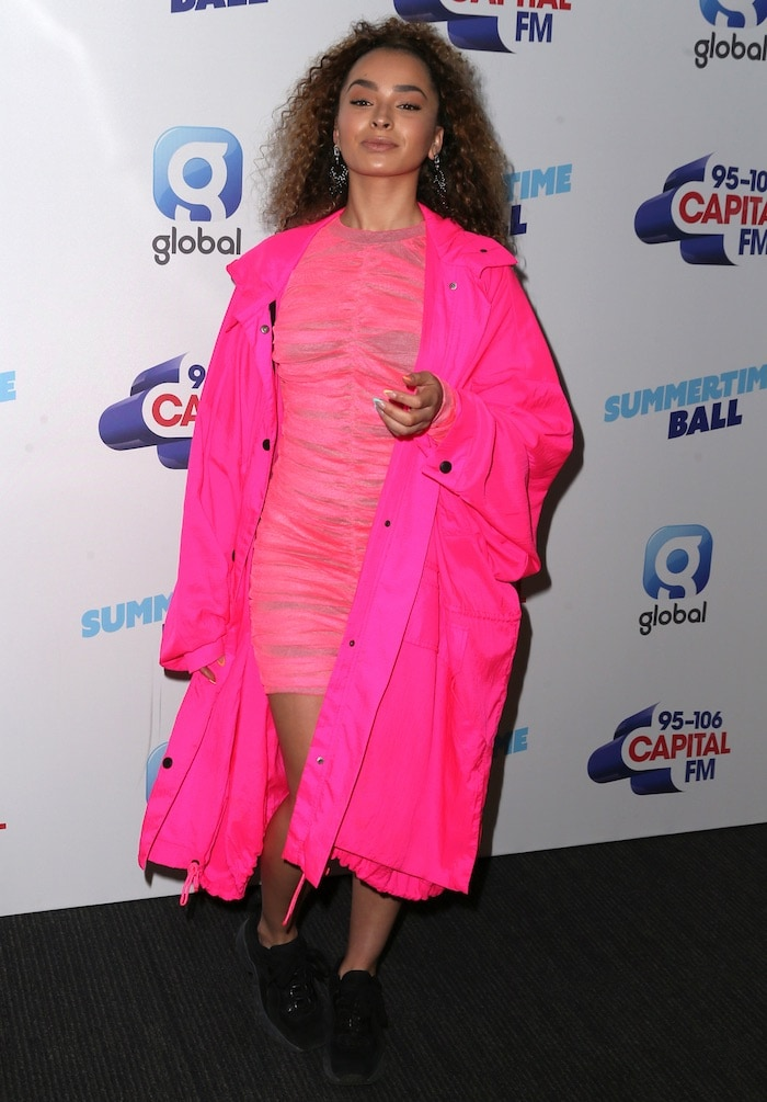 Ella Eyre in a hot pink bodycon dress and oversized raincoat