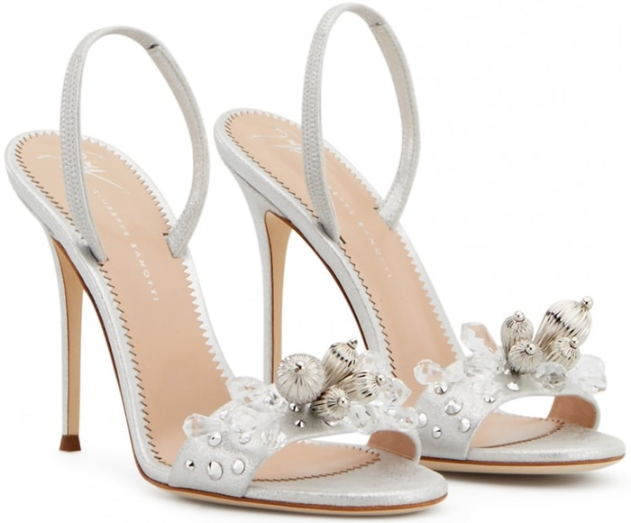 Crafted from copper shooting patent leather, these sandals are set on a stiletto heel