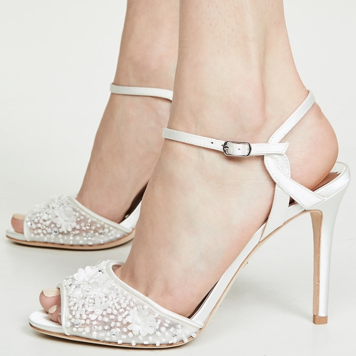 Twinkling beads, crystals and flower appliqués embellish the straps of a glamorous sandal lifted by a tall, tapered heel