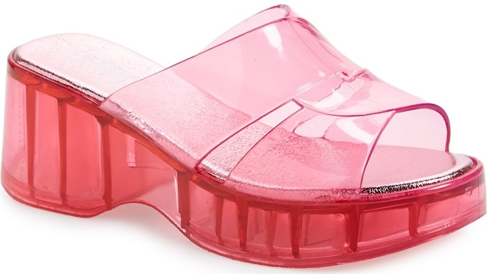 A curvy platform and chunky flared heel ramp up the look of a wedge-profile slide sandal molded in old-school jelly style