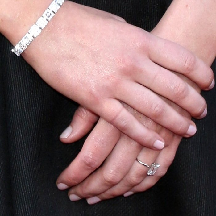 Jennifer Lawrence's emerald-cut diamond engagement ring on a delicate band