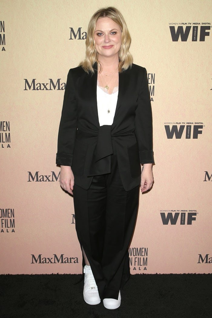 Amy Poehler in a black Max Mara pantsuit and white Nike sneakers