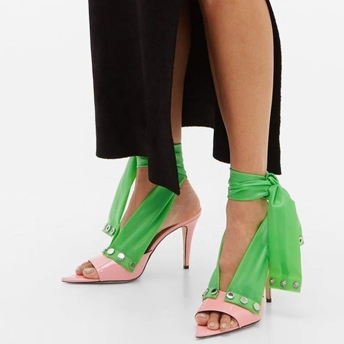 Crafted in Italy, these pink mules from Christopher Kane are comprised of exaggerated green ankle straps that are set with engraved silver-tone metal buttons, then set on a high stiletto heel