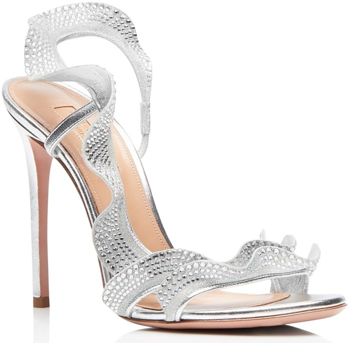 Made in Italy from laminata nappa in shimmery silver, the strappy style features a flirty ruffle adorned with glittering crystals that cascades up the foot and wraps around the ankle