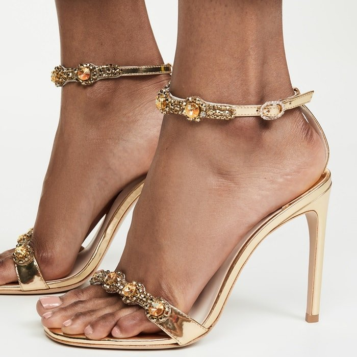 Sophia Webster's feminine and playful energy is echoed in these opulent gold Aaliyah sandals