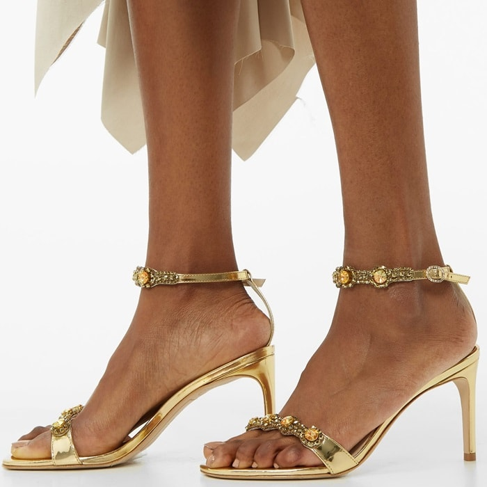 These sandals are crafted from glossy patent leather with slender toe and heel straps embellished with circular crystals, then set on a slender stiletto heel