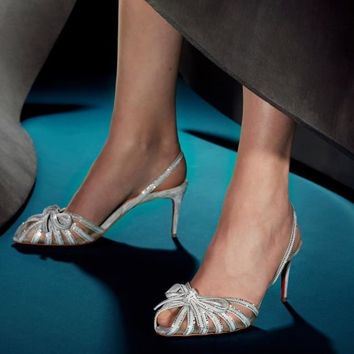 Rows of tiny crystals enhance the effervescent attitude of a slingback sandal featuring fanned-out straps at the mesh vamp topped with a pert bow