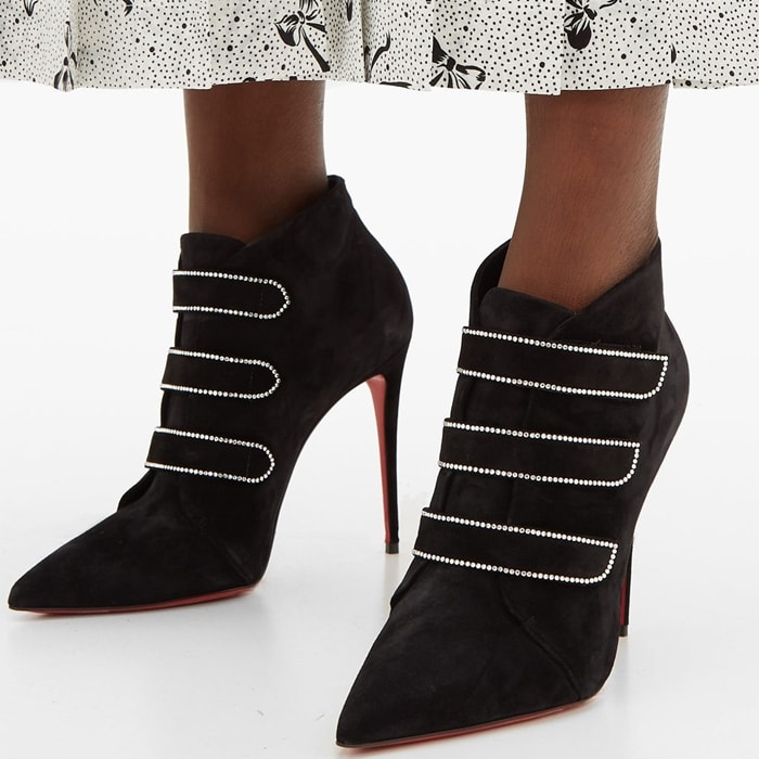 The Triniboot 100 silhouette from Christian Louboutin sits atop stiletto heels, finishes with pointed toes, and is finished with a trio of decorative straps running over the front