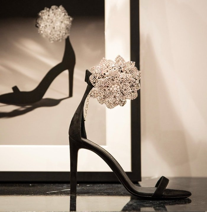 These high-heel, black suede sandals are characterized by the crystal flower accessory on the side