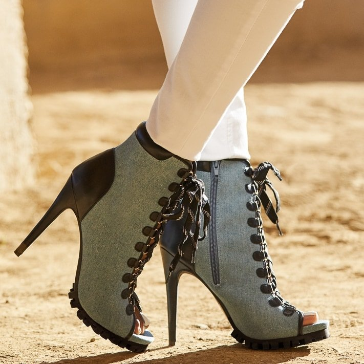A platform peep-toe hiker bootie with a stiletto heel, lug sole, adjustable laces, and zipper closure
