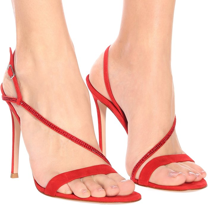Crafted in Italy from bright red suede, the design has a minimalist profile with thin straps – one of which is embellished with sparkling crystals