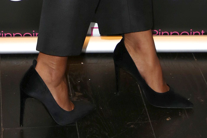 Laura Harrier's sexy feet in black satin pumps that appear to have been altered from their original ankle-strap style