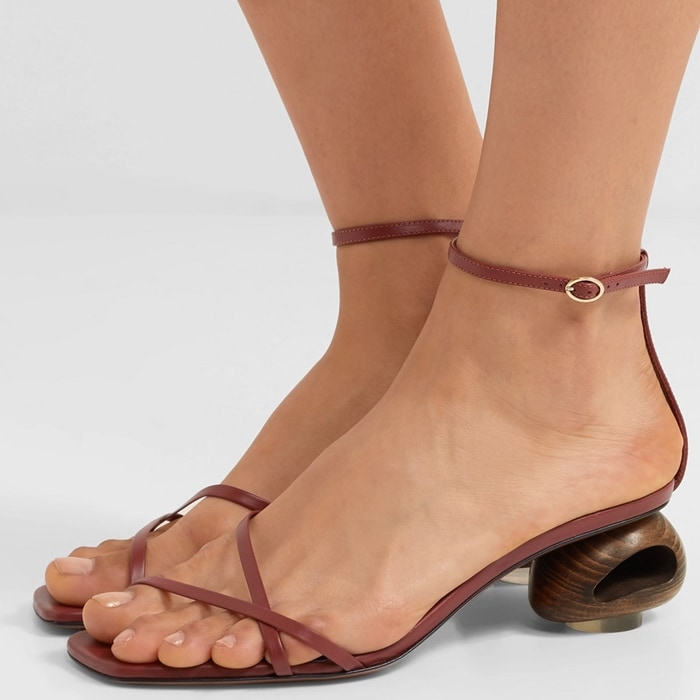 These dog poop sandals are propped on a pebble-shaped wooden heel with an acrylic disc at the base