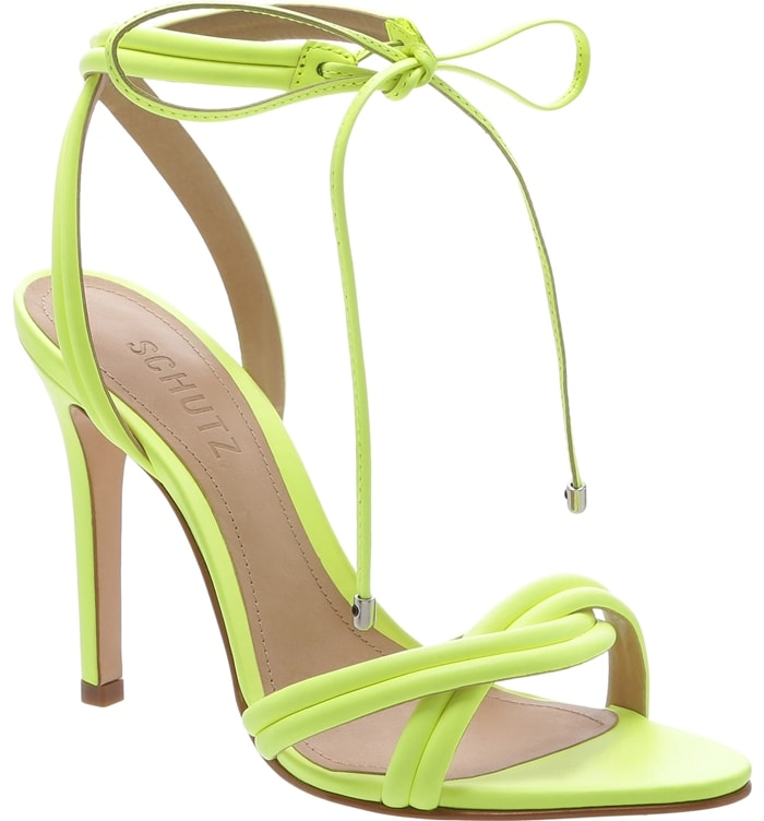 Plump, segmented straps entwine over the toe and wrap above the ankle of a towering leather neon yellow sandal finished at the front with a metal-tipped bow