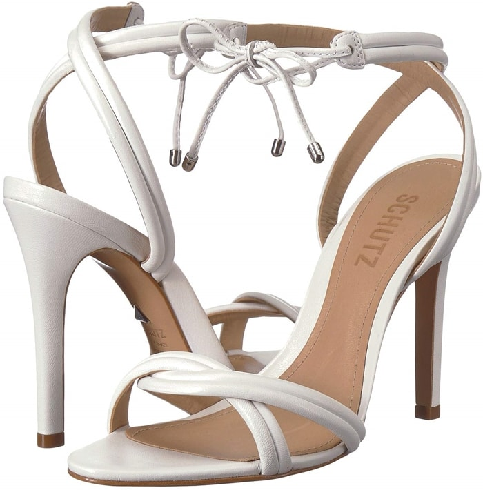 Plump, segmented straps entwine over the toe and wrap above the ankle of a towering white leather sandal finished at the front with a metal-tipped bow