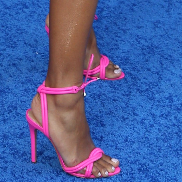 Serayah's hot feet in neon pink twisted leather ankle-tie Yvi sandals