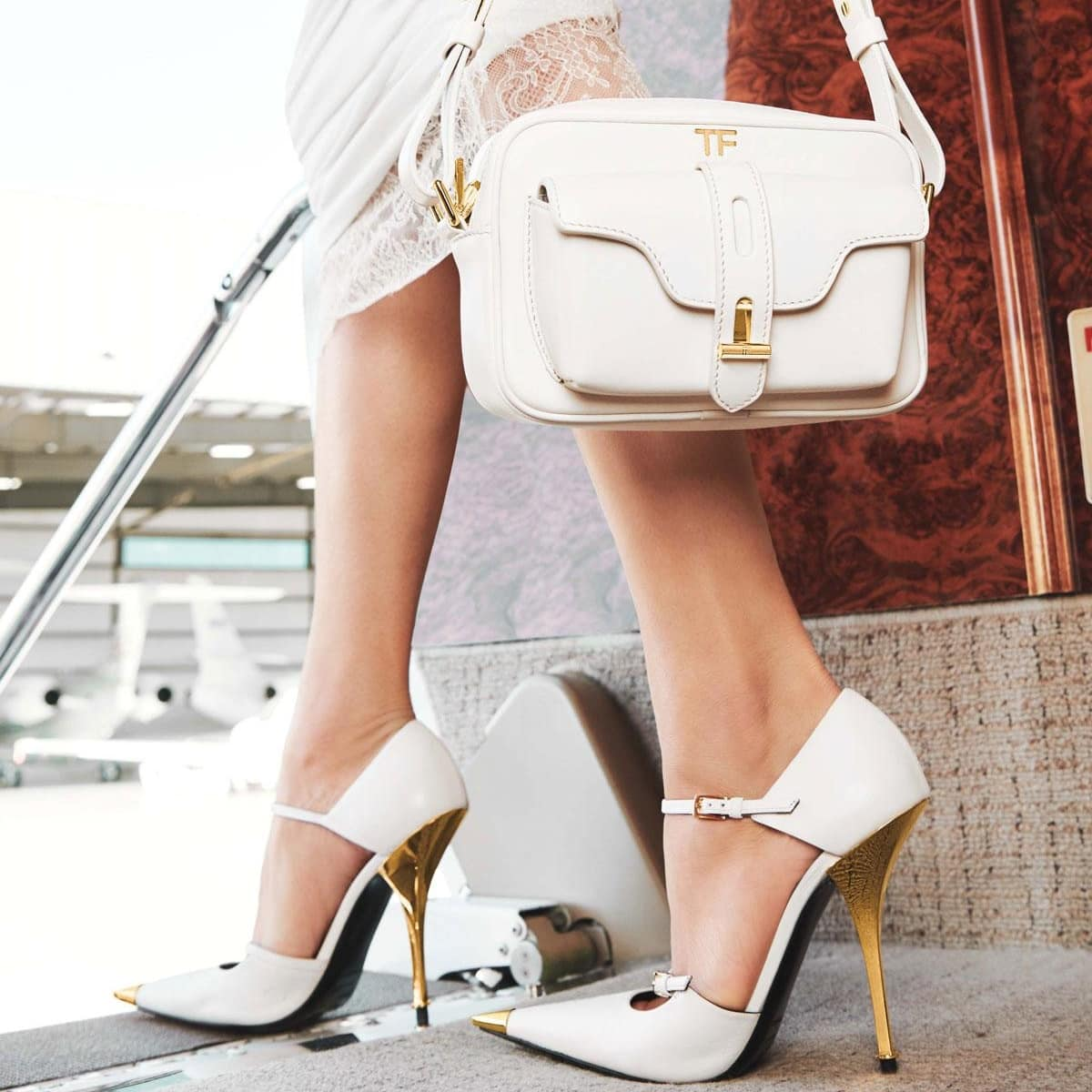 White camera crossbody bag and two-strap Mary Jane pointy-toe metal toe pumps