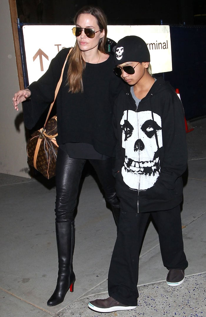 Angelina Jolie wearing Louboutin boots and an LV bag at LAX