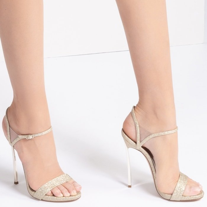The ankle strap with vinyl triangle and the remarkable Blade heel give the illusion of longer legs