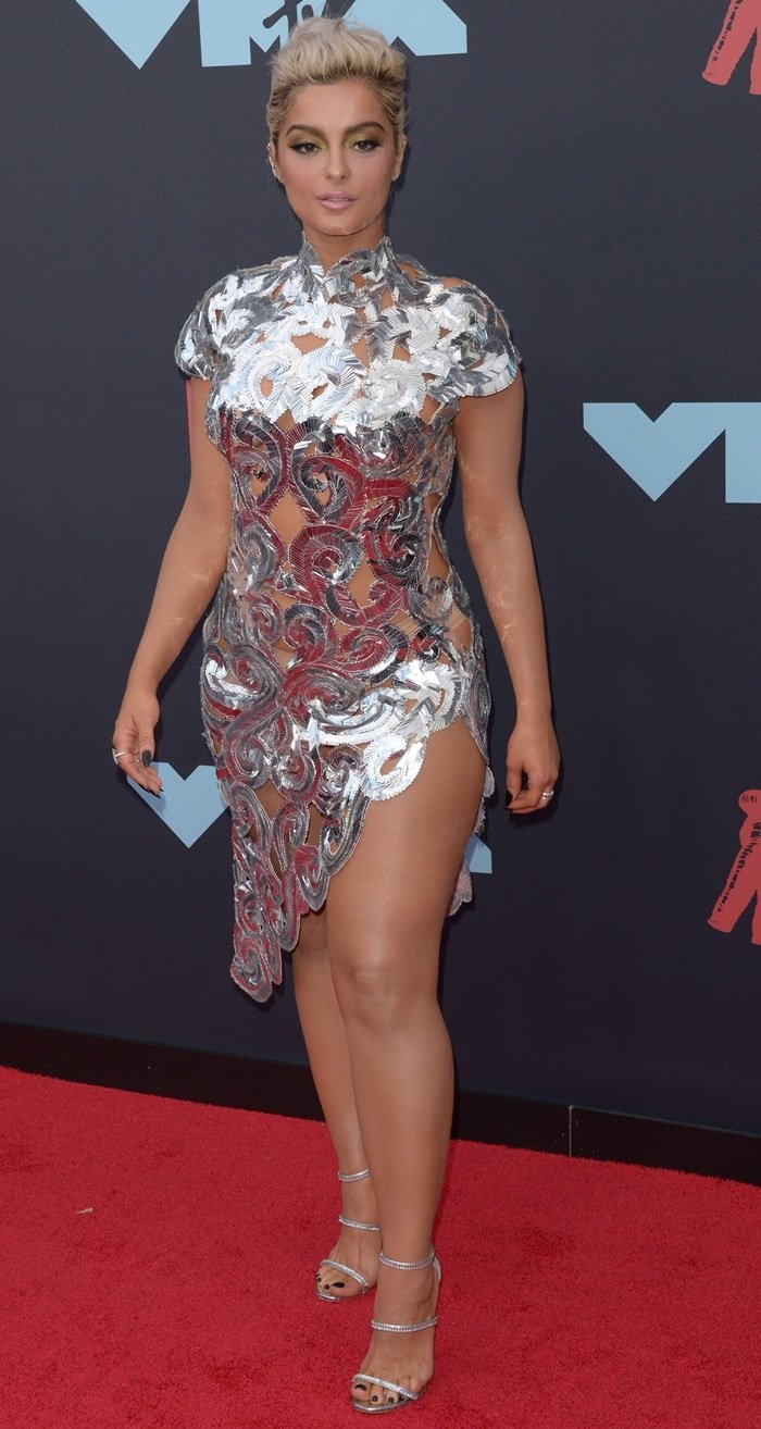 Bebe Rexha flaunted her 5′ 5″ (165 cm) frame in a metallic silver dress from Christian Siriano