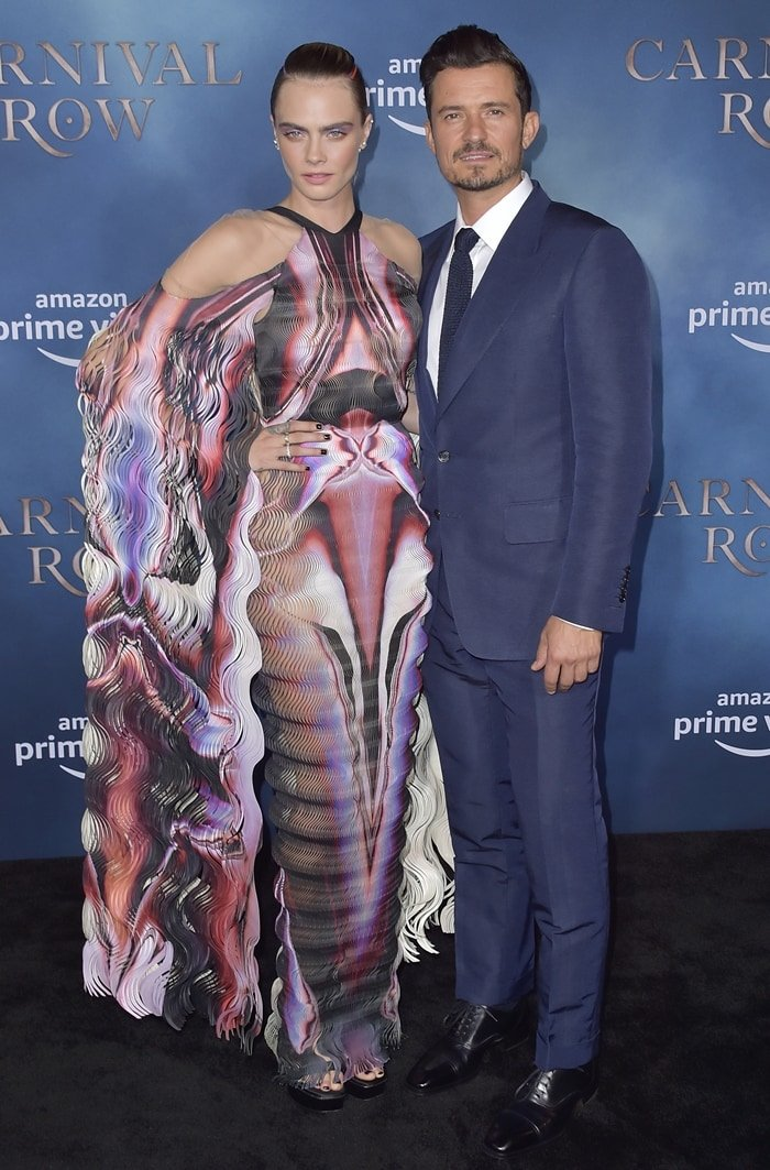 Cara Delevingne strikes a pose on the black carpet with her co-star Orlando Bloom at the premiere of Carnival Row