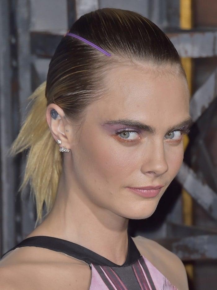 Cara Delevingne's purple-and-orange makeup and low ponytail
