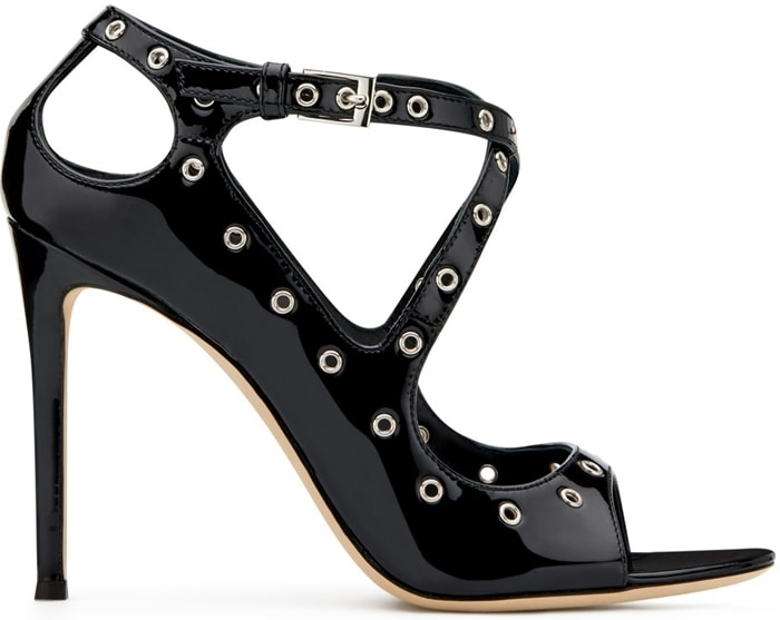 These high-heel, peep toe black patent sandals are characterized by the crossing design of their ankle strap, as well as by the decorative metal loops along the straps and the sides