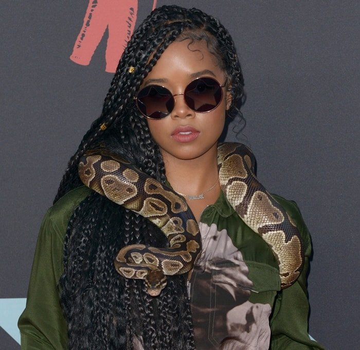 Gabriella Wilson, known professionally as H.E.R., with a python wrapped around her shoulders