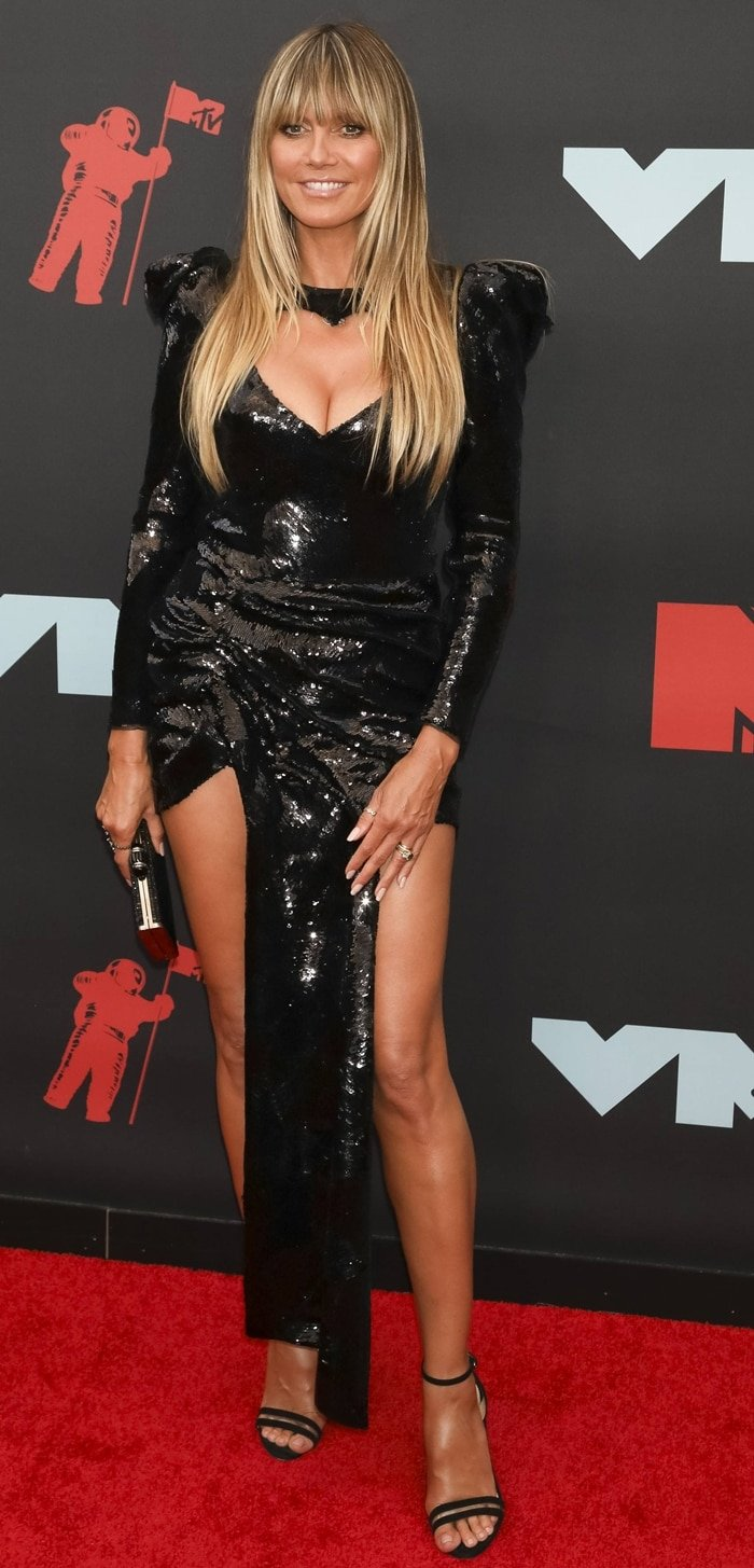 Heidi Klum paraded her long legs in a black sequined dress from Nedo by Nedret Taciroglu
