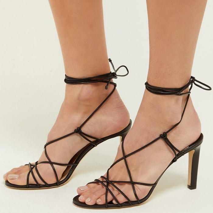 These black leather Tao sandals feature an open toe, a strappy design, a wrap tie ankle fastening, a branded insole, and a high heel