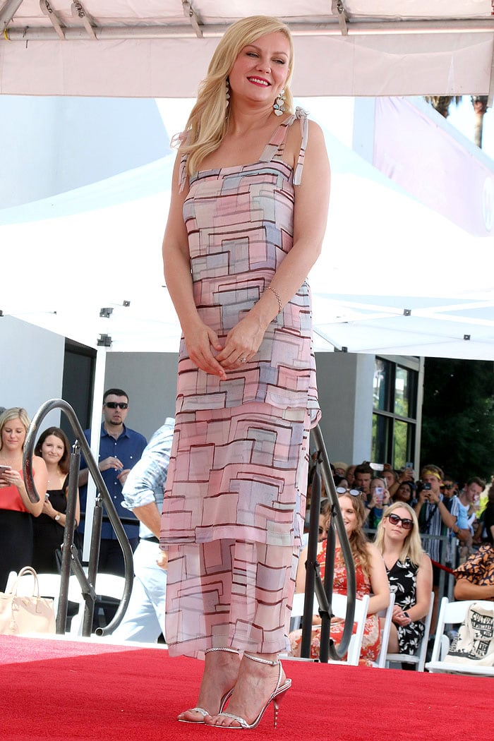 Kirsten Dunst in a Chanel Resort 2020 tiered geometric print dress and Gucci braided sandals
